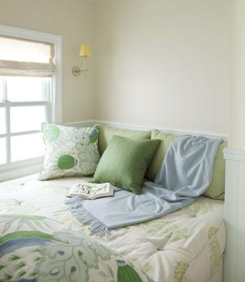 ghế cửa sổ với khăn trải giường màu xanh lá cây